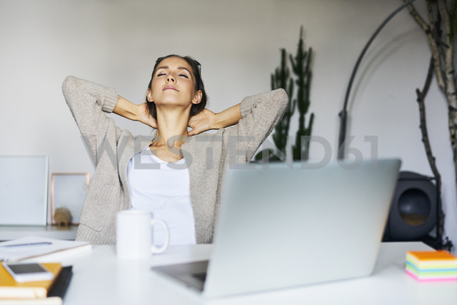 Young woman at home with laptop on desk leaning back - BSZF00170