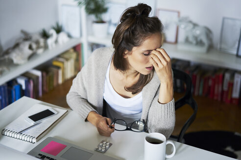 Young woman at home at desk suffering headache - BSZF00182
