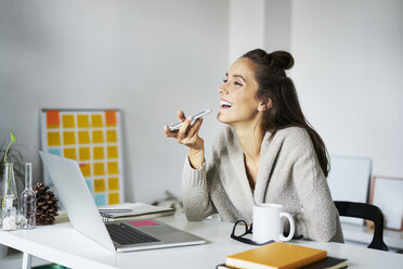Happy young woman using smartphone at desk - BSZF00185