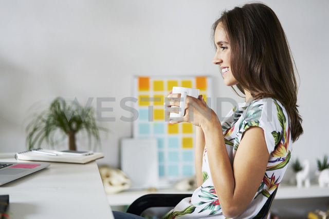 Smiling young woman drinking coffee at desk - BSZF00188