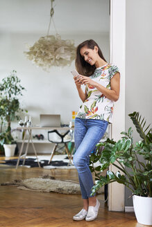 Smiling young woman using smartphone at home - BSZF00191