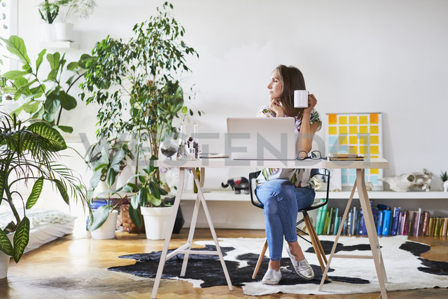 Young woman at home at desk looking sideways - BSZF00194