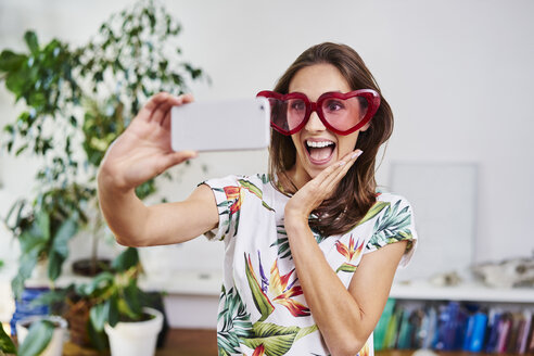 Happy young woman in heart-shaped glasses taking selfie - BSZF00197