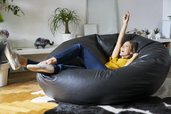 Happy young woman relaxing at home in beanbag - BSZF00200