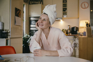 Portrait of smiling woman wearing a towel turban sitting with cup of coffee at table in the kitchen - MFF04374