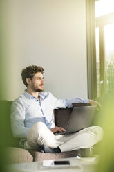 Man sitting on couch at home with laptop - SBOF01261