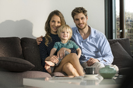 Portrait of smiling parents and son sitting on sofa at home - SBOF01264