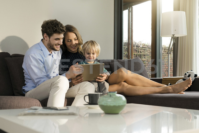 Parents and son sitting on sofa holding tablet at home - SBOF01270