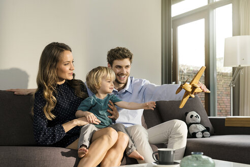 Happy parents and son playing with wooden toy plane on sofa at home - SBOF01273