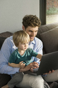 Father and son looking at laptop on couch at home - SBOF01276