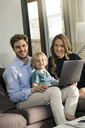 Portrait of happy parents and son sitting on sofa with laptop at home - SBOF01279
