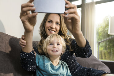 Smiling mother with son taking a selfie on sofa at home - SBOF01285