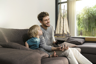 Father and son with toy model ship on couch at home - SBOF01288