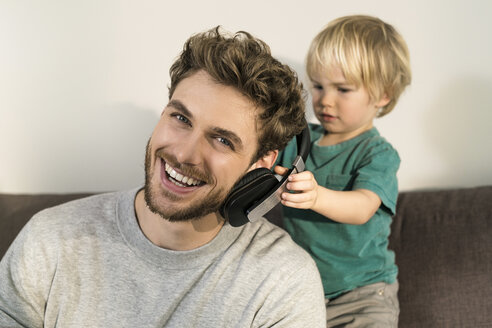 Happy father and son with headphones on couch at home - SBOF01291