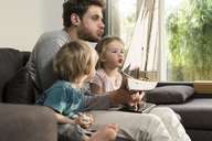 Father and children blowing into sails of toy model ship on couch at home - SBOF01297