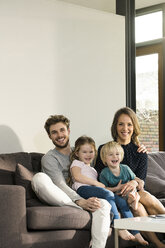 Portrait of happy family sitting on sofa at home - SBOF01300