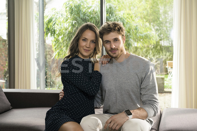Portrait of smiling couple sitting on sofa at home with view to garden - SBOF01303 - Steve Brookland/Westend61