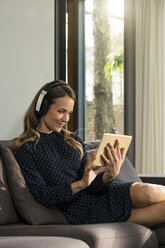 Smiling woman with tablet and headphones relaxing on couch at home - SBOF01306