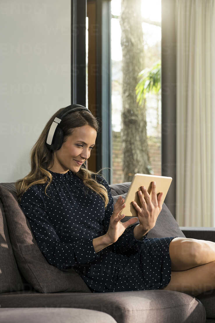 Smiling woman with tablet and headphones relaxing on couch at home - SBOF01306 - Steve Brookland/Westend61