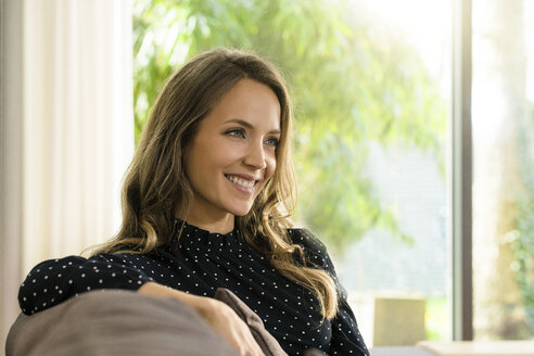 Portrait of smiling woman relaxing on couch at home - SBOF01309