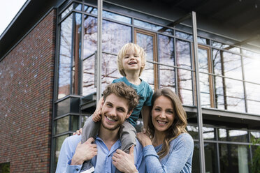 Portrait of smiling parents with son in front of their home - SBOF01312
