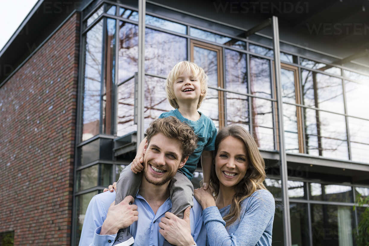 Portrait of smiling parents with son in front of their home - SBOF01312 - Steve Brookland/Westend61