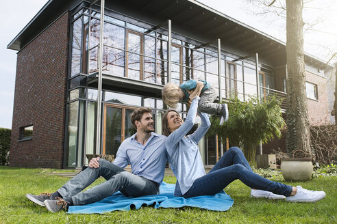 Happy parents with son sitting on blanket in garden in front of their home - SBOF01315