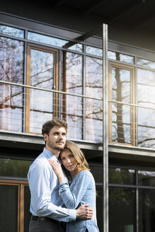 Affectionate couple embracing in front of their home - SBOF01318