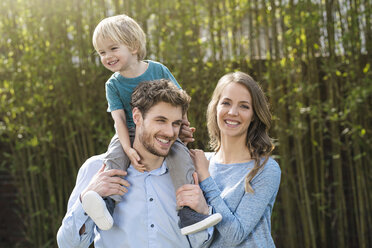 Portrait of happy family in garden in front of bamboo plants - SBOF01321