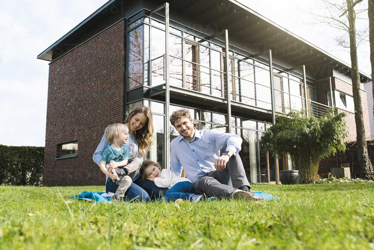 Portrait of smiling family on blanket in garden in front of their home - SBOF01324 - Steve Brookland/Westend61