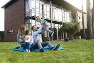 Happy family on blanket in garden in front of their home with father litfting up son - SBOF01327