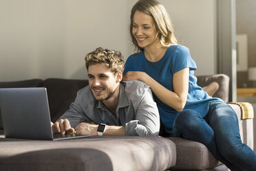 Smiling couple using laptop on sofa at home - SBOF01330