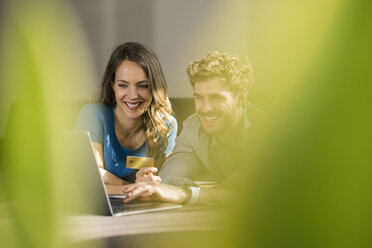 Smiling couple shopping online with laptop on sofa at home - SBOF01333