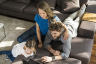 Family using laptop on sofa at home - SBOF01336