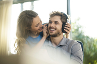 Smiling woman putting on headphones on boyfriend - SBOF01339