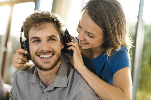 Smiling woman putting on headphones on boyfriend - SBOF01342