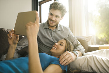 Smiling couple looking at tablet and relaxing on sofa at home - SBOF01345