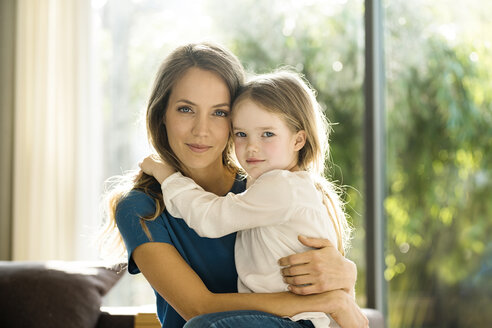 Portrait of smiling mother holding her daughter at home - SBOF01348