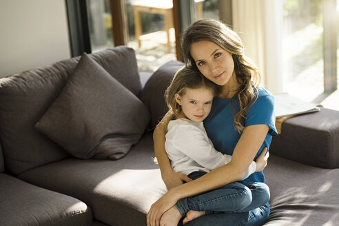 Portrait of smiling mother holding her daughter on sofa at home - SBOF01351