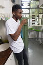 Young man in the kitchen drinking from glass - LFEF00030