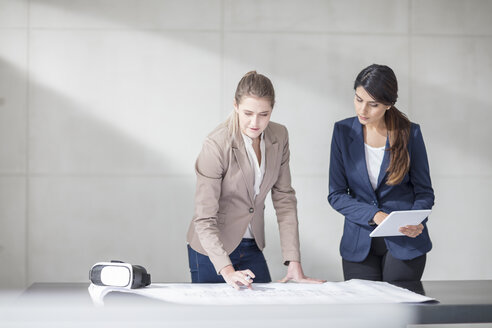 Two young women with tablet and VR glasses working on blueprint in office - ZEF14908