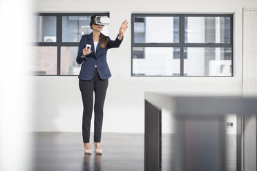 Businesswoman wearing VR glasses in office - ZEF14911