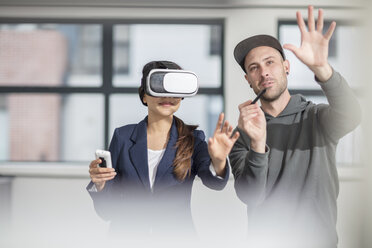 Man instructiong businesswoman wearing VR glasses in office - ZEF14914