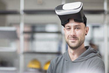 Portrait of smiling young man wearing VR glasses in office - ZEF14917