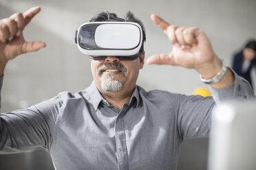 Man wearing VR glasses in office - ZEF14923