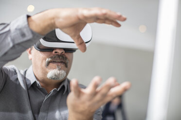 Man shaping with his hands wearing VR glasses in office - ZEF14926
