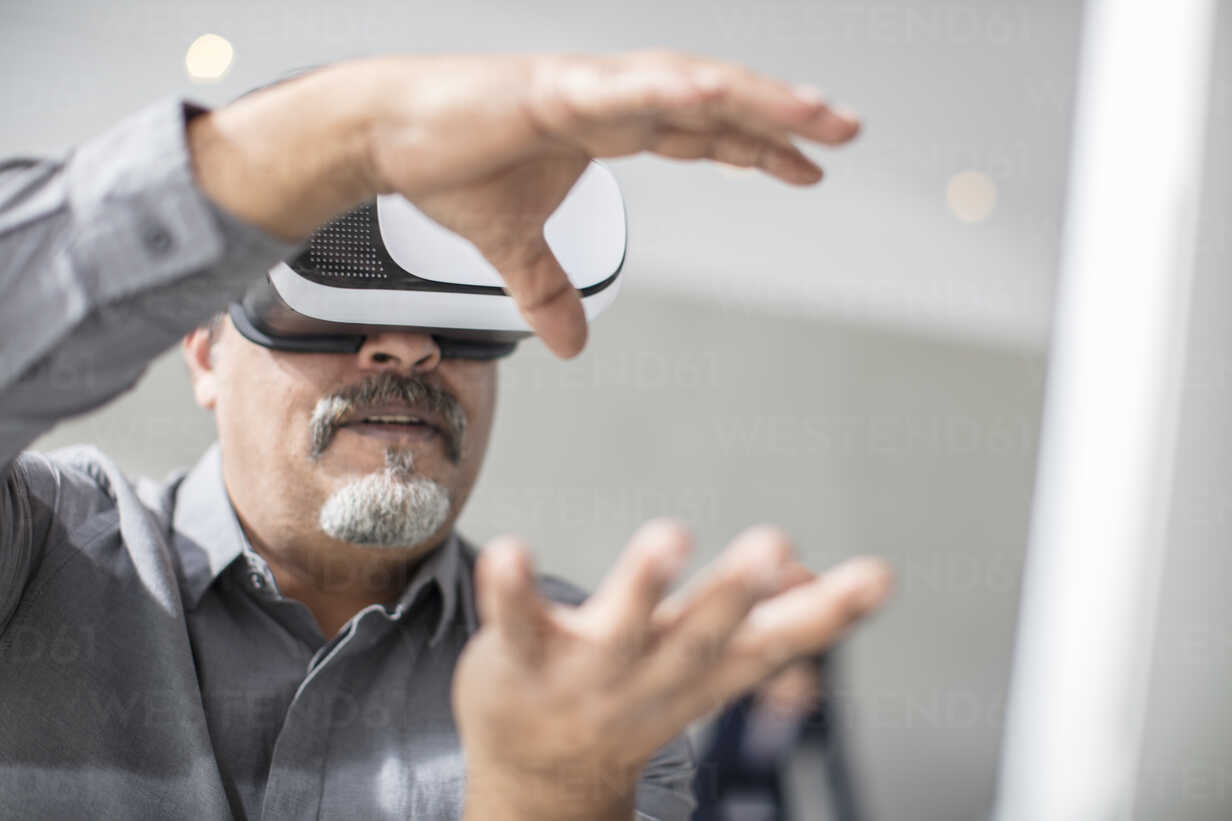 Man shaping with his hands wearing VR glasses in office - ZEF14926 - zerocreatives/Westend61