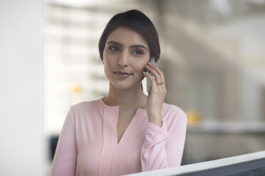 Portrait of young woman on cell phone in the office - ZEF14929