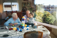 Great-grandparents and baby girl playing together with plastic building bricks at home - GEMF01859