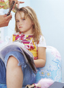 Hands of hairdresser combing and cutting hair of unhappy little girl - FSF00992
